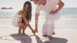 Couple writing on the sand