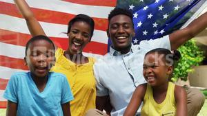 Family smiling and posing with the American flag