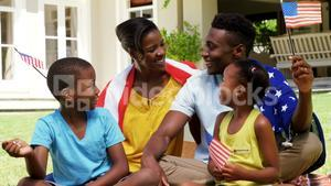 Family smiling and holding small American flags