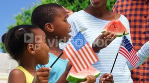 Family eating watermelon and holding American flags