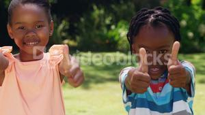 Children smilling with thumbs up