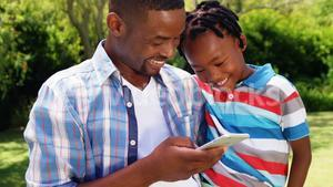 Man showing to his son pictures in the mobile phone