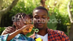 Little boy doing soap bubble with his father