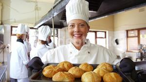 Female chef holding bun in cooling tray