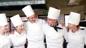 Group of chefs standing together with arms around
