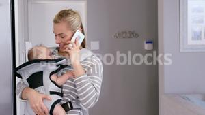 Mom using phone while carrying her baby