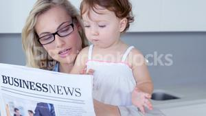 Blonde mother reading newspaper with her baby at hone
