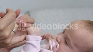 Close up of cute baby holding mothers finger