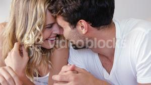 Couple relaxing on bed in bedroom
