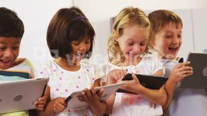 children laughing and using tablet computer