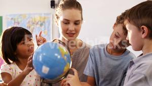 pupils and teacher in classroom with globe