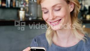 Smiling woman is watching her phone