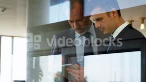 Two men watching a tablet