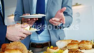 Two men talking together with a plate in their hand