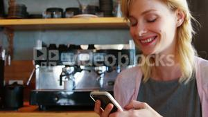 Smiling woman watching her smartphone