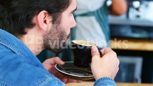 Focus of man is drinking coffee at counter
