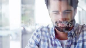 Portrait of young hipster is using a tablet and looking away