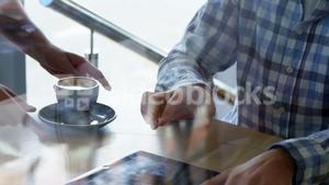 Waiter bringing coffee to young hipster
