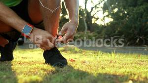 Man tying his shoe laces while jogging in park