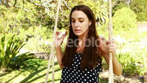 Young woman using asthma inhaler while swinging in park