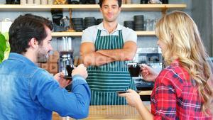 Waiter serving coffee to customer