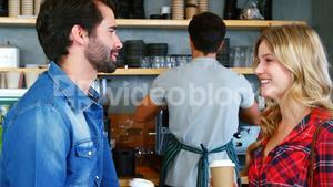 Young couple interacting and holding disposable coffee cup