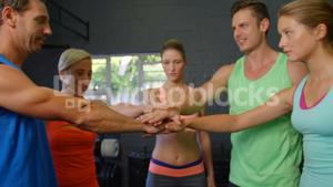 Fitness trainer and gym member putting hands together