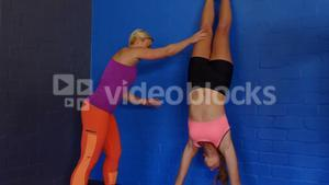 Fitness trainer assisting woman to perform handstand