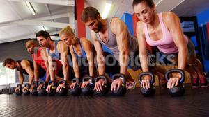 Group of people performing push-up exercise with kettlebell