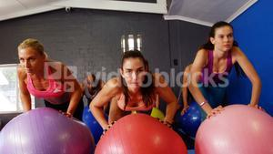Beautiful fit women exercising on fitness ball