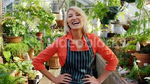 Happy mature woman smiling in greenhouse
