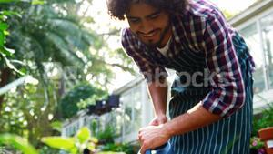 Man watering plant with watering can