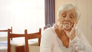 Unhappy senior woman sitting alone
