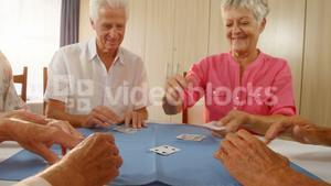 Happy senior friends playing cards