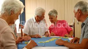 Senior friends talking while playing dominos