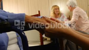 Doctor holding hands of a senior woman sitting in wheelchair