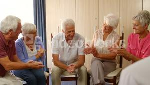 Group of senior friends clapping hands