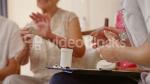 Senior woman with a pill box talking to the therapist