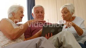 Senior friends discussing together with a digital tablet