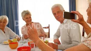Woman photographing her senior friends