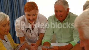 Doctor watching senior people playing cards