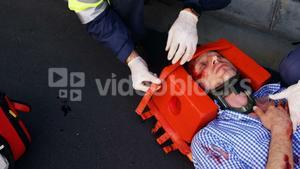 Emergency medical technician protecting the head of his wounded person