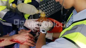 Emergency medical technician taking the pulse of his wounded person