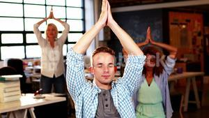 Business people meditating in yoga pose