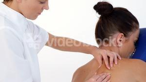 Profile view of therapist woman massaging the back of her patient