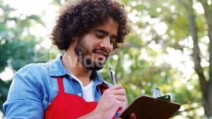 Gardener thinking and writing on clipboard