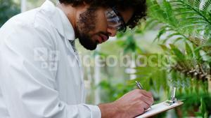 Man taking notes of plants on clipboard