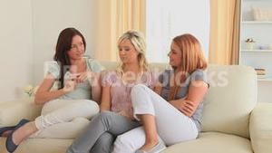 Women chatting while sitting on a sofa
