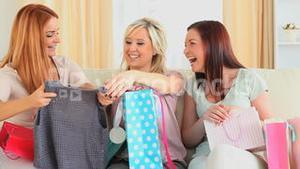 Cute woman showing new clothes to her friends