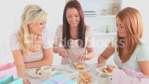 Young women eating a cake